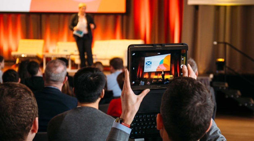Man in audience taking photo of DataTalent stage on his tablet
