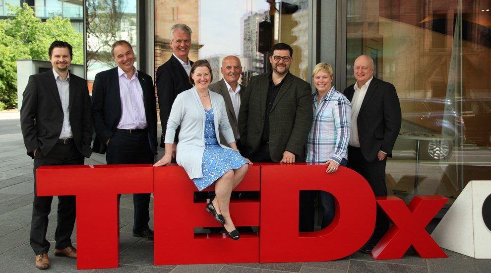 Group standing round and sitting on large red TEDx letters