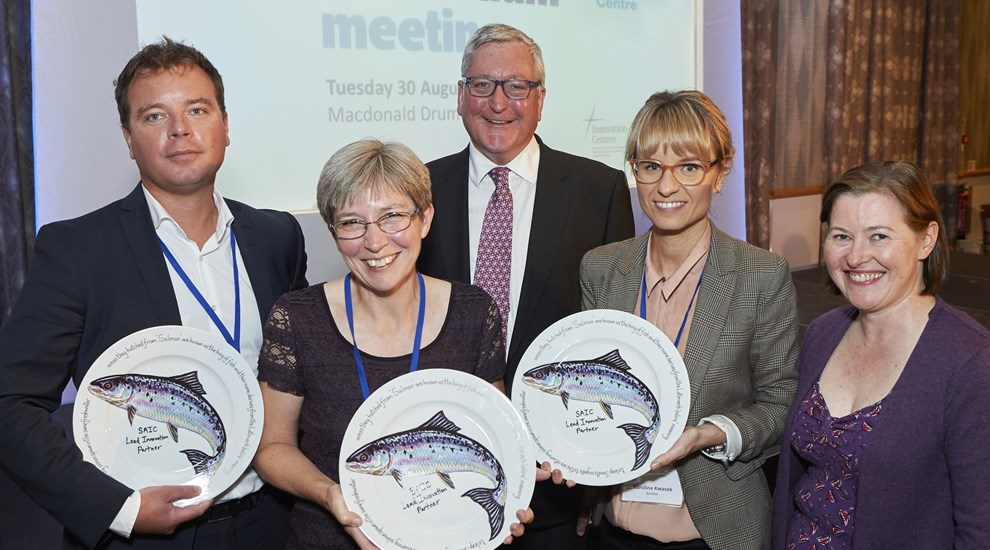 Photo of SAIC group holding 3 round plates with picture of salmon on them