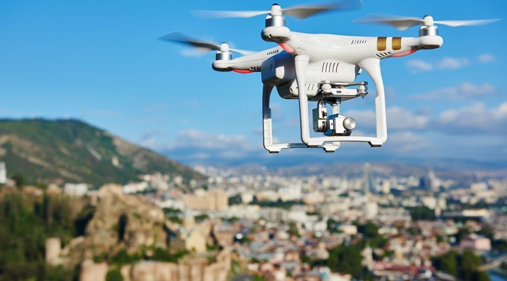 Photo of white drone in flight over city