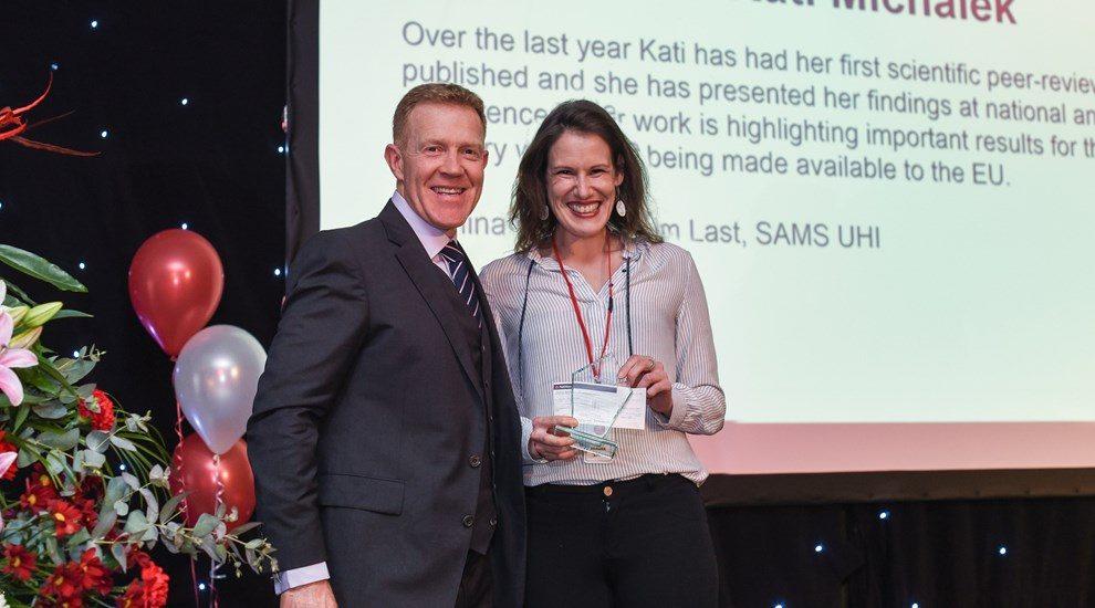 Kati Mickalek receiving award with Adam
