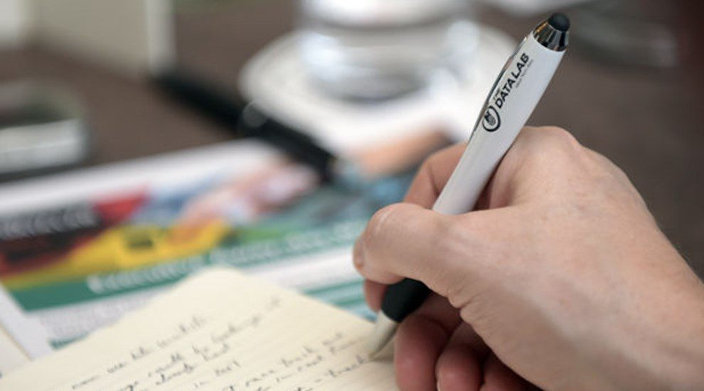 Photo of hand writing with The Data Lab pen