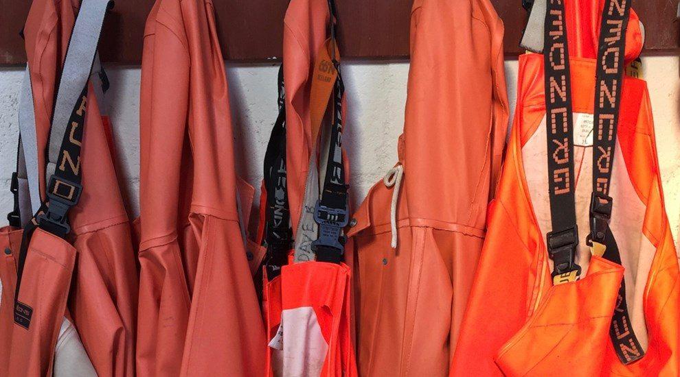 Photo of orange waterproofs hanging on pegs