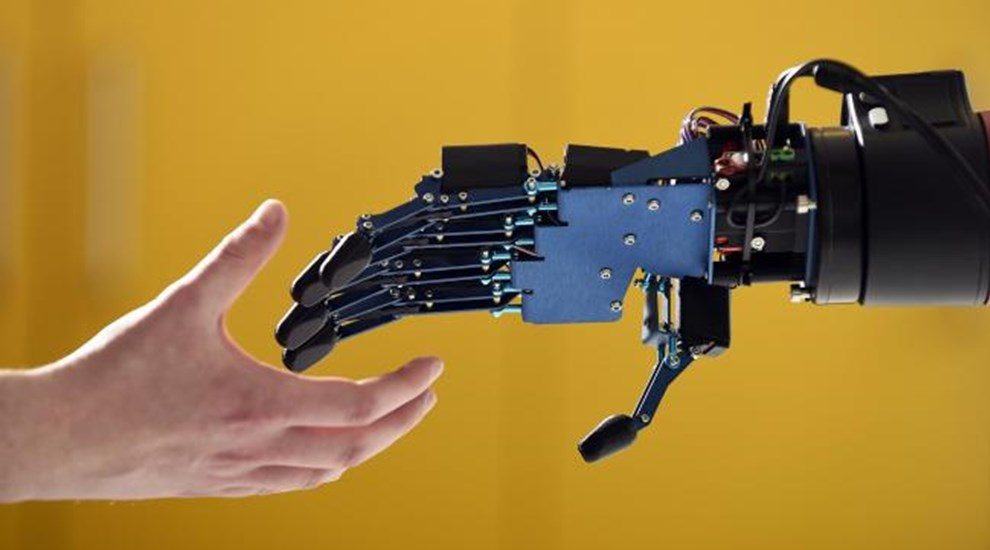 Photo of human hand reaching for robotic hand